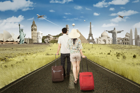 asian boy: Couple walking on the road while carrying luggage to trip the famous landmarks Stock Photo