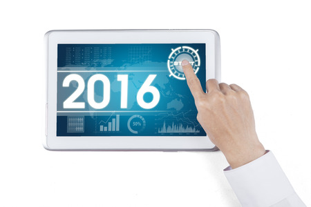 economic forecast: Hand touching digital tablet with the economic forecast for 2016