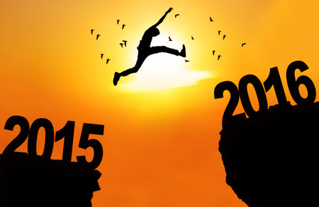 cliff: Silhouette of young man jumping over a cliff with numbers 2015 and 2016 at sunset time