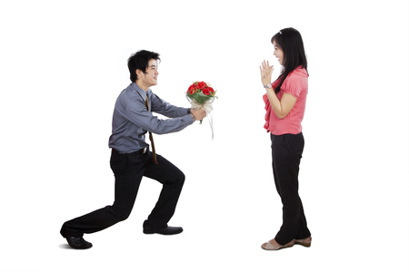 woman surprise: Young romantic man giving bunch of roses to his girlfriend, isolated on white background