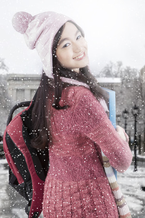 girl studying: Pretty young student with winter clothes smiling on the camera at the school