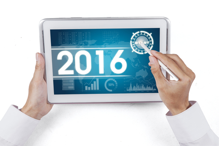 economic forecast: Hand using stylus pen for touching digital tablet with the economic forecast for 2016