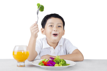 asia children: Happy boy eating broccoli with fork isolated on white background