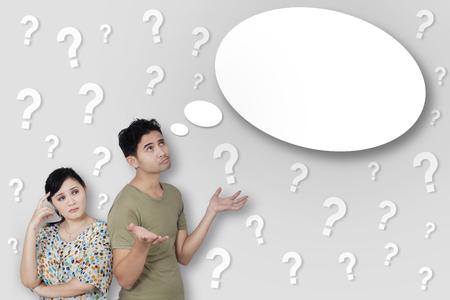 punto interrogativo: Ritratto di giovane coppia riflessivo con molti punti interrogativi