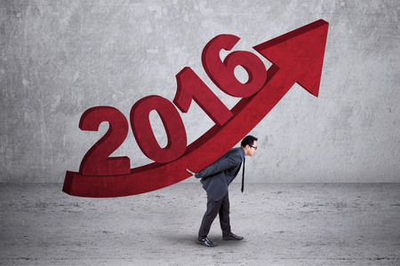 upward: Image of young businessman carrying upward arrow with numbers 2016