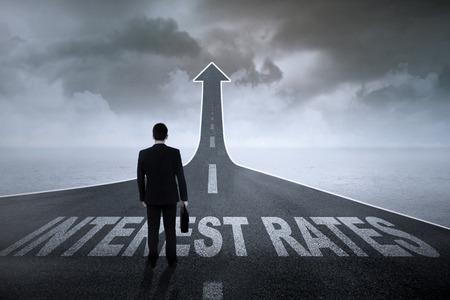 Homme d'affaires debout sur la route se transforme en une flèche avec des taux d'intérêt mots sur elle