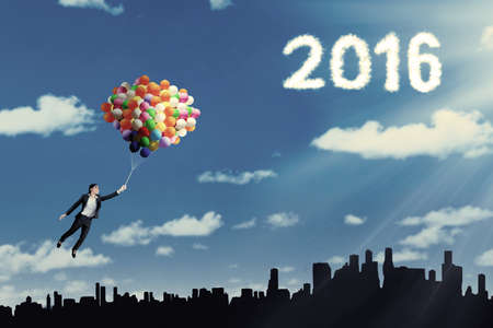 pursue: Young businesswoman using balloons to fly over the city with cloud shaped numbers 2016
