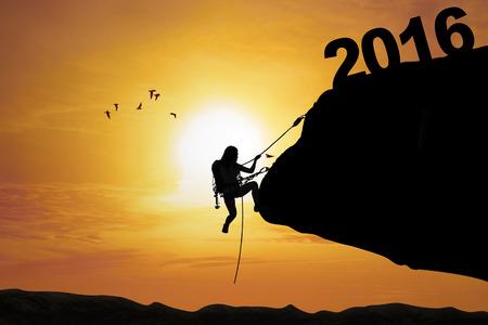 silueta humana: Silueta de la mujer joven que sube un acantilado en la puesta del sol con los n�meros 2016