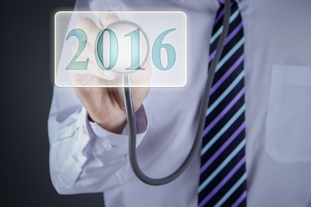 heal new year: Male doctor touching virtual button on the virtual screen with numbers 2016