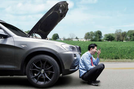 car breakdown: Angry young man waiting a help while sitting near the broken car at the side of road Stock Photo