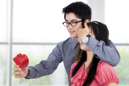 gives: Happy chinese man gives a gift to a young woman from the back Stock Photo