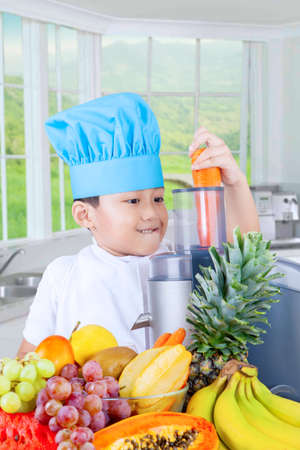 extractor: Little boy making fresh and healthy juice with a juice extractor in the kitchen
