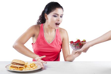 niña comiendo: Retrato de niña india con la fresa hamburguesa rechazar, aislado en fondo blanco Foto de archivo