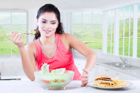 healthy foods: Indian woman making decision between healthy food and fast food at home Stock Photo