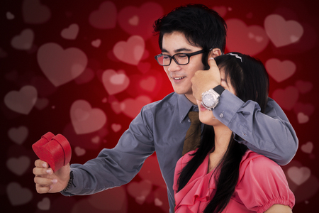 covering: Portrait of young Chinese man giving a gift to his girlfriend while covering her eyes, shot with love background