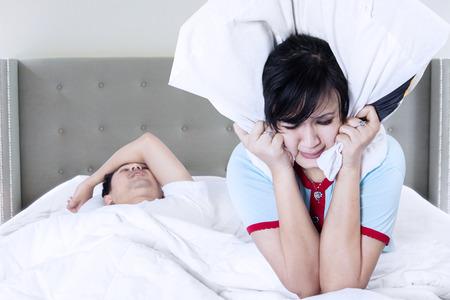 Portret van een jonge man snurken met zijn vrouw kan niet slapen en die oren met kussen voor snurken lawaai Stockfoto