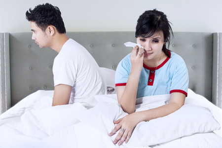 chinese sex: Young asian woman sitting on bed while crying and sweep her tear after quarrel with her husband