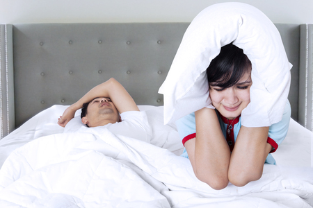 Image of young man sleeping on bed and snoring while his wife can not sleep and use pillow to cover her ears