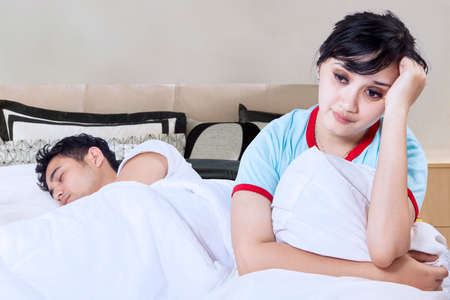 chinese sex: Picture of pretty woman having problem with her husband and looks stressed in the bedroom