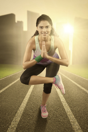 woman foot: Young indian woman doing exercise and standing with one feet at the field Stock Photo