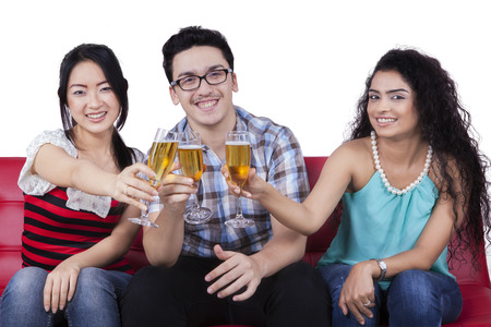 girl sitting: Portrait of three multiracial people sitting on the sofa while enjoy champagne and toasts together