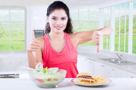choosing: Young woman choosing between junk food and vegetables salad on kitchen