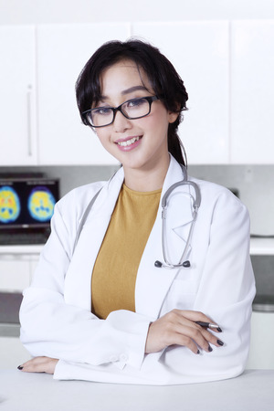 medical doctor: Beautiful female asian doctor smiling at the camera while wearing glasses and uniform in the clinic