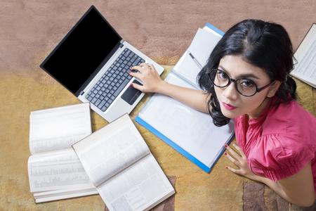 fille indienne: Gros plan de la belle élève du secondaire couché sur le tapis tout en regardant la caméra avec un ordinateur portable et des livres