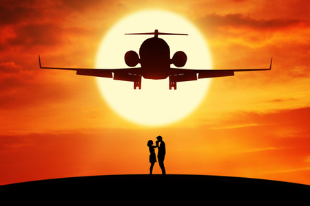 lady fly: Silhouette of romantic couple standing on the hill under a flying aircraft at sunset time Stock Photo