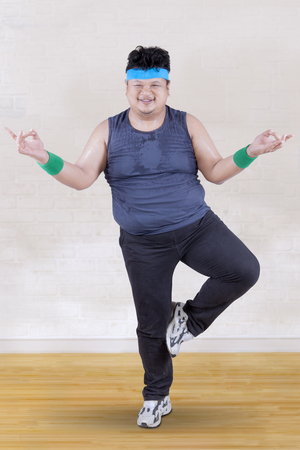 asian abs: Picture of overweight person doing workout at home while standing with one feet