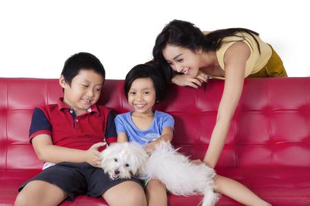 niños sentados: Imagen de niños felices que se sientan en el sofá mientras jugaba su cachorro con mamá, disparó en casa