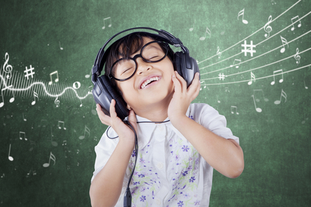 Female primary school student wearing glasses and smiling while listening music in the classroom Stock Photo