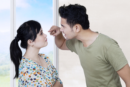 Afbeelding van een jonge man ruzie met zijn vrouw thuis, terwijl schreeuwen en schelden zijn vrouw