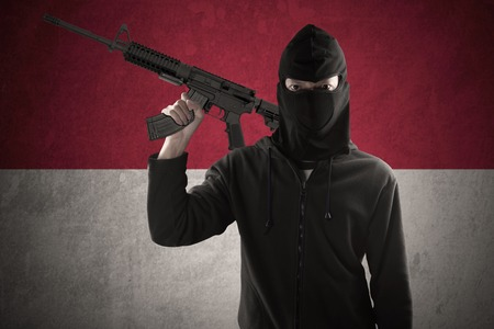 undisclosed: Male terrorist wearing mask and holding a machine gun in front of Indonesian flag