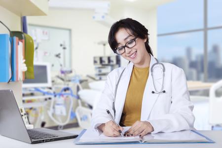 dentist: Imagen de bastante joven dentista que trabaja en la clínica, mientras que escribe la prescripción con el ordenador portátil sobre la mesa