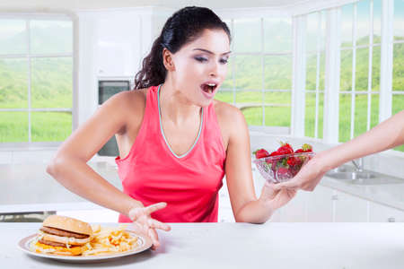 woman eat: Young beautiful indian girl making choice between hamburger and strawberry in a bowl