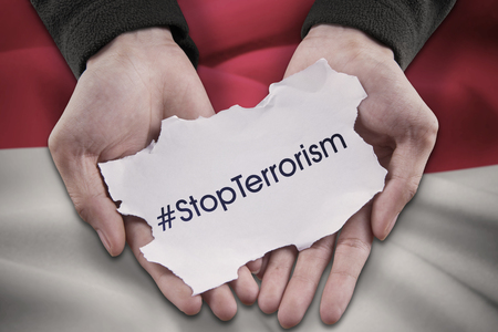 the indonesian flag: Close up of two hands holding a paper with #stopterrorism in front of Indonesian flag