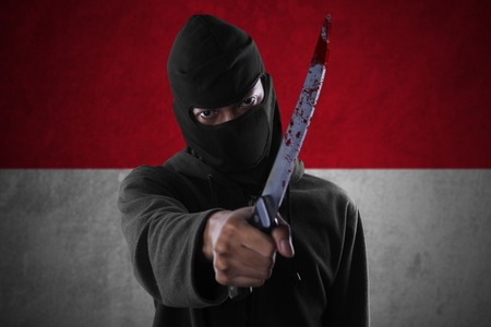 guerrilla: Image of male terrorist using a bloody knife for threatening in front of Indonesian flag