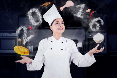 woman cooking: Portrait of indian female chef wearing uniform and cooking like a juggler