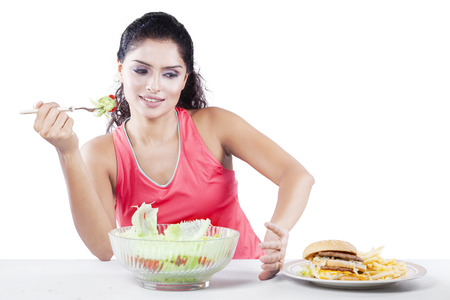 junk food: Indian girl refuse to eat junk food and choose vegetable salad, isolated on white background Stock Photo