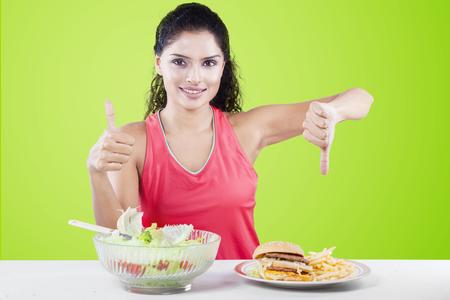 niña comiendo: Mujer india elegir entre ensalada de verduras y comida rápida