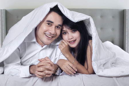 boyfriend: Photo of two happy couple lying under blanket in the hotel room while smiling at the camera