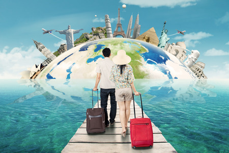 pier: Young couple walking on the pier while carrying luggage toward a globe with famous landmark in the world Stock Photo