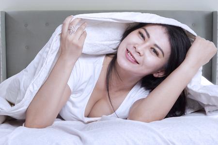 despertarse: Foto de mujer joven atractiva, acostado en la cama bajo la manta blanca y sonriendo a la cámara
