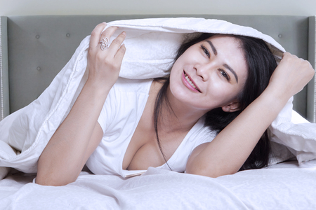 wake: Photo of attractive young woman lying in the bedroom under white blanket and smiling at the camera