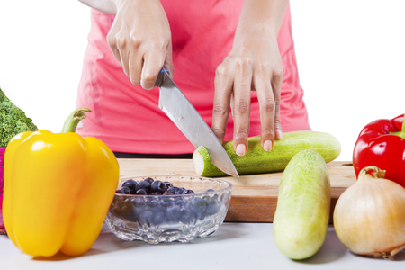 cutting vegetables: Female hands cutting vegetables, isolated on white background