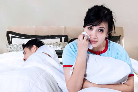 chinese sex: Picture of young woman having problem with her husband and crying on bed while her husband sleeping Stock Photo