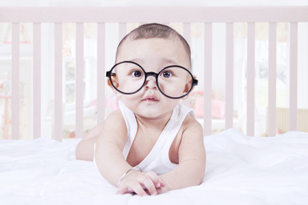 kids wear: Portrait of male baby boy lying on the bedroom while wearing glasses and looking at the camera Stock Photo