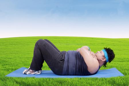 obesidad: Persona con sobrepeso acostado en el colchón mientras vistiendo ropa deportiva y haciendo ejercicio en el prado Foto de archivo