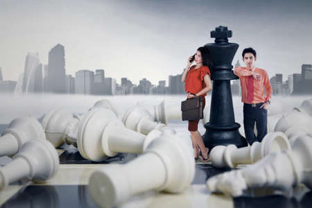 pawn adult: Portrait of two young businesspeople standing on the chessboard and lean on the black chess queen